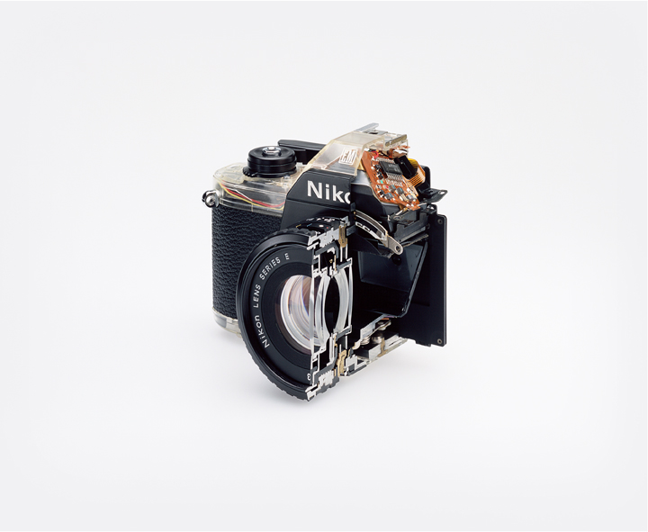 Christopher Williams (American, born 1956). Cutaway model Nikon EM. Shutter: / Electronically governed Seiko metal blade shutter vertical travel with speeds from 1/1000 to 1 second with a manual speed of 1/90th. / Meter: Center-weighted Silicon Photo Diode, ASA 25-1600 / EV2-18 (with ASA film and 1.8 lens) / Aperture Priority automatic exposure / Lens Mount: Nikon F mount, AI coupling (and later) only / Flash: Synchronization at 1/90 via hot shoe / Flash automation with Nikon SB-E or SB-10 flash units / Focusing: K type focusing screen, not user interchangeable, with 3mm diagonal split image rangefinder / Batteries: Two PX-76 or equivalent / Dimensions: 5.3 × 3.38 × 2.13 in. (135 × 86 × 54 mm), 16.2 oz (460g) / Photography by the Douglas M. Parker Studio, Glendale, California / September 9, 2007– September 13, 2007. 2008. Chromogenic color print. Paper: 20 x 24″ (50 .8 x 61 cm), framed: 29 15/16 x 37 3/16″ (76 x 94.5 cm). The Museum of Modern Art, New York. Acquired through the generosity of Helen Kornblum in honor of Roxana Marcoci and Committee on Photography Fund. Courtesy of the artist; David Zwirner, New York/London; and Galerie Gisela Capitain, Cologne © Christopher Williams