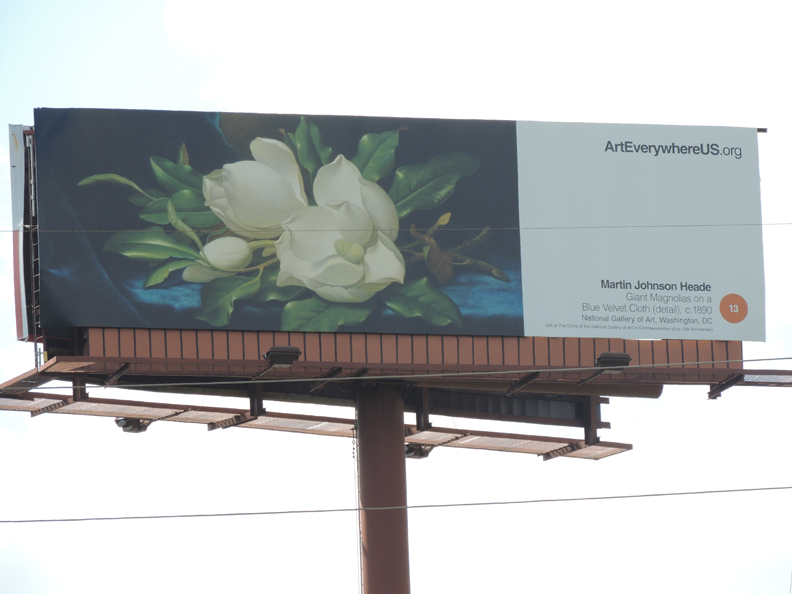 Art Everywhere US billboard, featuring Martin Johnson Heade's Giant Magnolias on a Blue Velvet Cloth (1890, National Gallery of Art, Washington DC, Gift of The Circle of the National Gallery of Art in Commemoration of its 10th Anniversary)