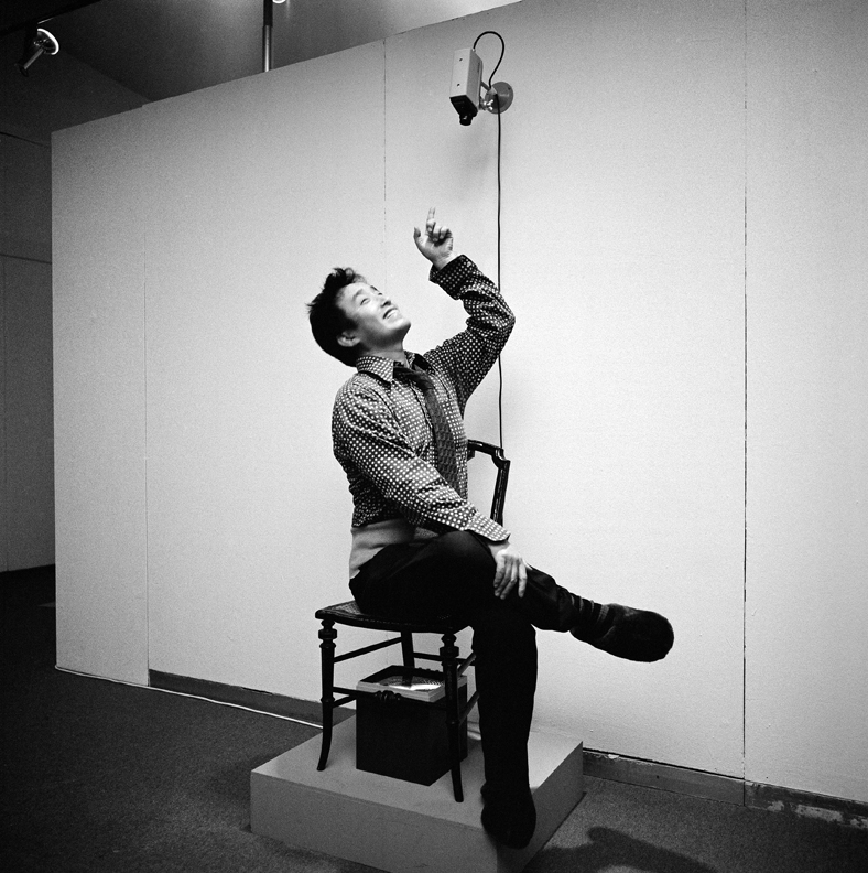 "Paik sitting in TV Chair (1968/1976) in ""Nam June Paik Werke, 1946–1976: Music, Fluxus, Video,"" 1976.  Photo credit: © Friedrich Rosenstiel, Cologne"