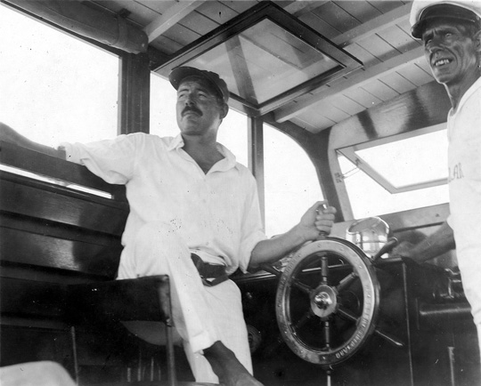 "EH8300 ca. 1934 Ernest Hemingway and Carlos Gutierrez aboard the Pilar. Inscribed on verso:""EH and Carlos at wheel of Pilar"" Location unknown. Copyright unknown. Please credit:""Ernest Hemingway Collection at the John F. Kennedy Presidential Library and Museum, Boston."""