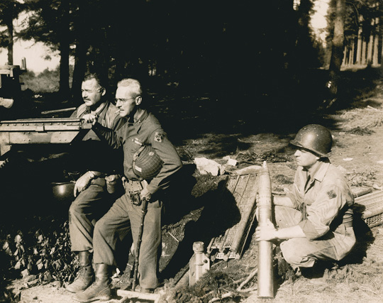 "EH3749P 18 September 1944 Ernest Hemingway stands in uniform beside Colonel Charles ""Buck"" Lanham, in Schweitzer Germany, WWII. An unidentified soldier kneels to hold ammunition."