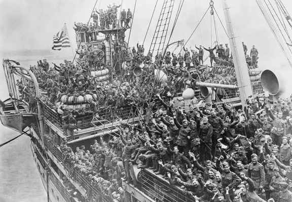 ca. 1919, Hoboken, New Jersey, USA --- Soldiers on the USS Agamemnon cheer as they return home from battles in France. The deck of the ship is crowded with cheering soldiers. Hoboken, New Jersey, ca. 1919. --- Image by © Corbis