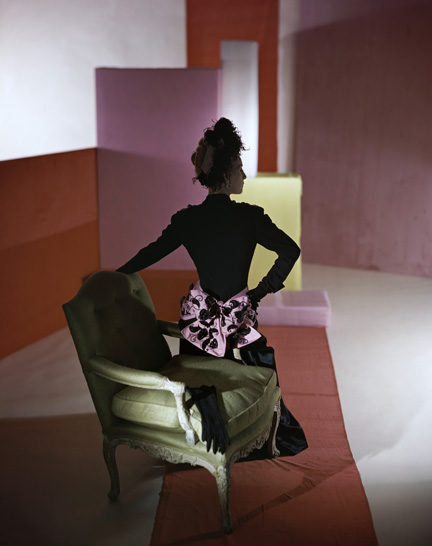 Model with her back to the camera sitting on the arm of a chair, wearing a black Schiaparelli dress with a large pink bow on the small of her back, a pair of black gloves are on the chair and in the background are large colored squares