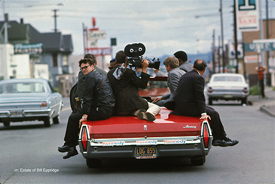 Sentator Robert F. Kennedy and the press ride a convertible through Oregon, April or May, 1968 Presidential campaign. Photograph by Bill Eppridge