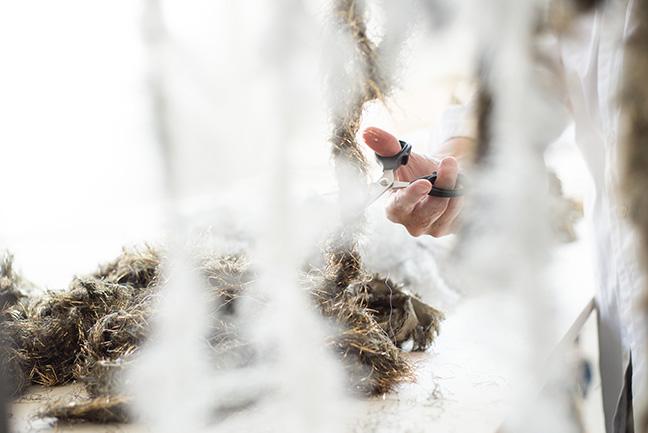 Preparing selvedges from Hosoo brocaded silk and metallic fabrics. Photo: © Luisa Cevese Riedizioni