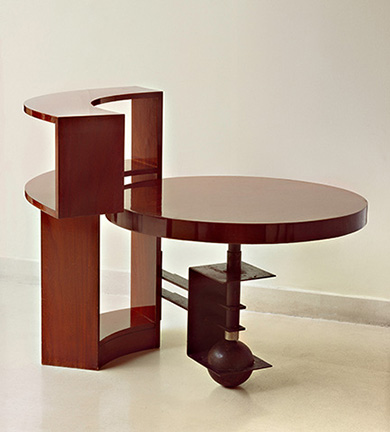 Table and bookcase (MB960), c. 1930, designed by Pierre Chareau, walnut and black patinated wrought iron, 36Ω x 45º x 8 in.; table: 23Ω in. high, 33æ diameter. Galerie Vallois Paris.