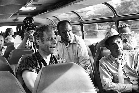 "Merce Cunningham, le cineaste Klaus Wildenham et John Cage (chapeau) dans un bus entre Paris et Hambourg en route pour les studios de la television Norddeutscher Rundfunk pour le tournage du ballet ""Variations V"" en 1966. On a cach from Paris to Hamburg for the shooting of Cunningham's Ballet""Variations V"", Merce Cunningham, movie maker Klaus Wildenham, John Cage(straw hat), 1966."